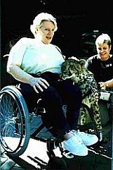 woman in wheelchair with cheetah cub
